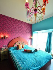 a colorful bedroom with a carved wooden bed, bright bedding, wall and chandelier and an ornate nightstand