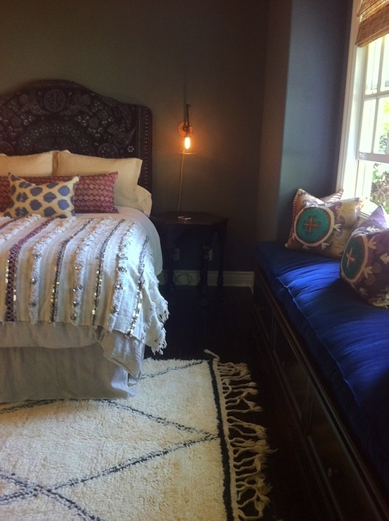 a moody Moroccan bedroom with an ornate headboard bed, a velvet upholstered seat and colorful cushions and bedding