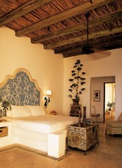 a neutral Moroccan bedroom with an ornate bed, a carved wooden chest with decor and a potted plant