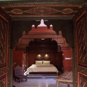 a small Moroccan bedroom in a beautiful alcove done in burgundy and gold, with lights and natural light from the window