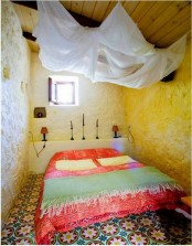 a Moroccan tile floor, bright bedding and candle holders add a strong Moroccan feel to the space
