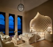 a luxurious Moroccan bedroom with a carved out headboard wall, Moroccan-inspired windows and a carved wooden table