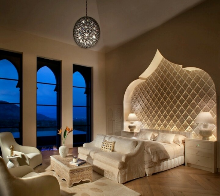 a luxurious Moroccan bedroom with a carved out headboard wall, Moroccan inspired windows and a carved wooden table