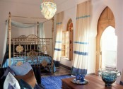 an elegant Moroccan bedroom done in blues and gold, with a gold bed, ornate wooden shutters and blue textiles here and there