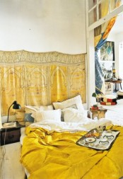 a small mustard-sprinkled bedroom with a blanket on the wall and matching bedding plus vintage nightstands