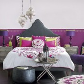 a Moroccan-inspired leather bed, lanterns, a leather ottoman and touches of purple and fuchsia make up a bold modern Moroccan bedroom