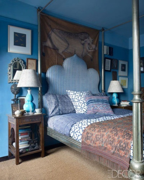 a Moroccan fele is given to the bedroom with a whimsy blue bed, carved wooden tables and ornate mirrors