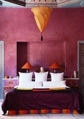a burgundy and fuchsia Moroccan bedroom with touches of orange and a Moroccan lantern