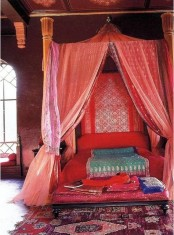 a red Moroccan bedroom with plenty of pattern, boho rugs and bedding and carved wooden furniture