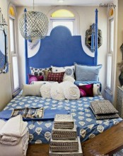 a small blue bedorom with an ornate bed, printed bedding and pillows, artworks and a lantern for an Eastern look