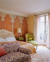 a colorful Moroccan bedroom done in rust, purple, neutrals and mustard and with traditional prints