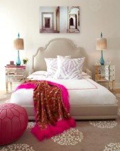 a pink Moroccan pouf, a printed rug and a catchy bed add a Moroccan feel to the sleeping space
