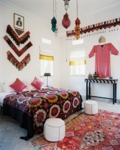 a colorful Moroccan bedroom with bright lanterns, printed rugs and bedding, a colorful artwork of fabric