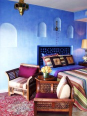 a carved bed and chairs, a Moroccan lantern and colorful printed textiles