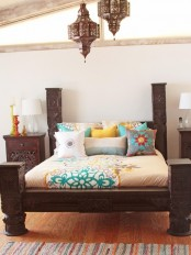 dark carved wooden furniture, Moroccan lanterns and colorful bedding to create a modenr Eastern sleeping space