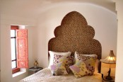 a red ornate shutter and a carved out headboard to add an Eastern feel to the bedroom