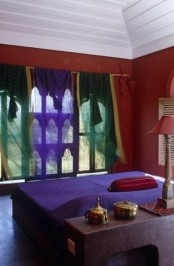 red combined with green and purple, a chic lamp and a catchy window with frames