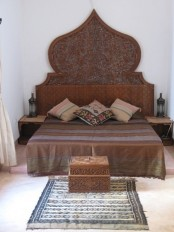 a statement carved owoden bed, nightstands and a chest plus catchy textiles create a chic Moroccan space