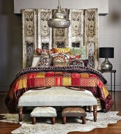an ornate wooden screen, elegant ottomans and bright printed textiles plus a hanging metal lantern
