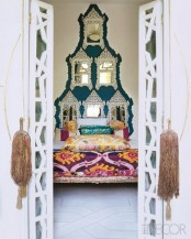 a unique wall decoration made of ornate mirrors, colorful bedding and tassels for a bright Eastern bedroom