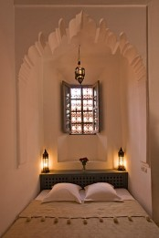 a small and neutral Moroccan bedroom in an alcove with a mosaic window, a storage headboard and lanterns