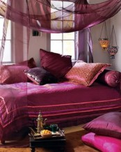 a bold purple and fuchsia bedroom with airy and sheer textiles, lanterns and a low table
