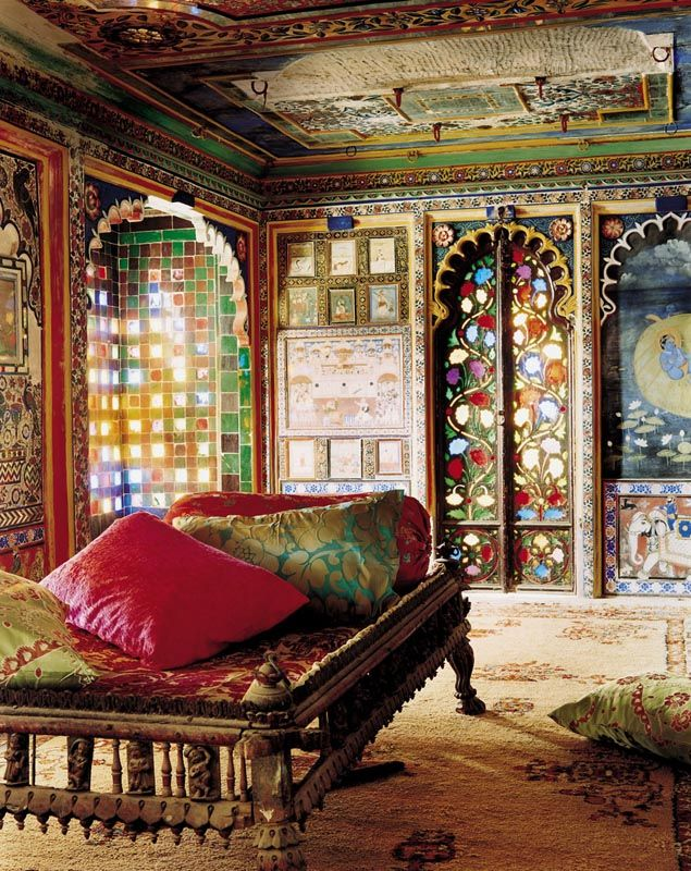 a super colorful Moroccan bedroom with lots of pattern, a beautiful ceiling, colorful pillows and rugs