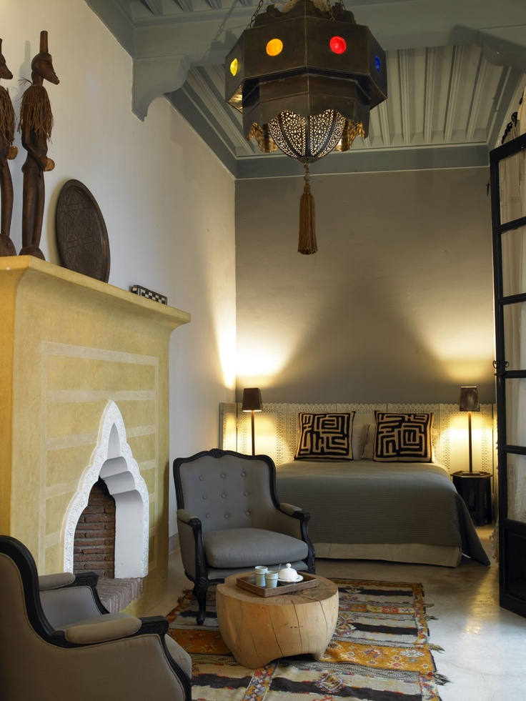a Moroccan lantern, a carved out fireplace, a boho rug and unique artworks give a modern space a bold look