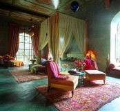 an ornate ceiling, bright textiles and rugs, metlalic lanterns and a bed with a tall frame