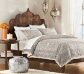 a reclaimed wodo carved bed, silver lanterns and ottomans make a rustic bedroom more Moroccan-like