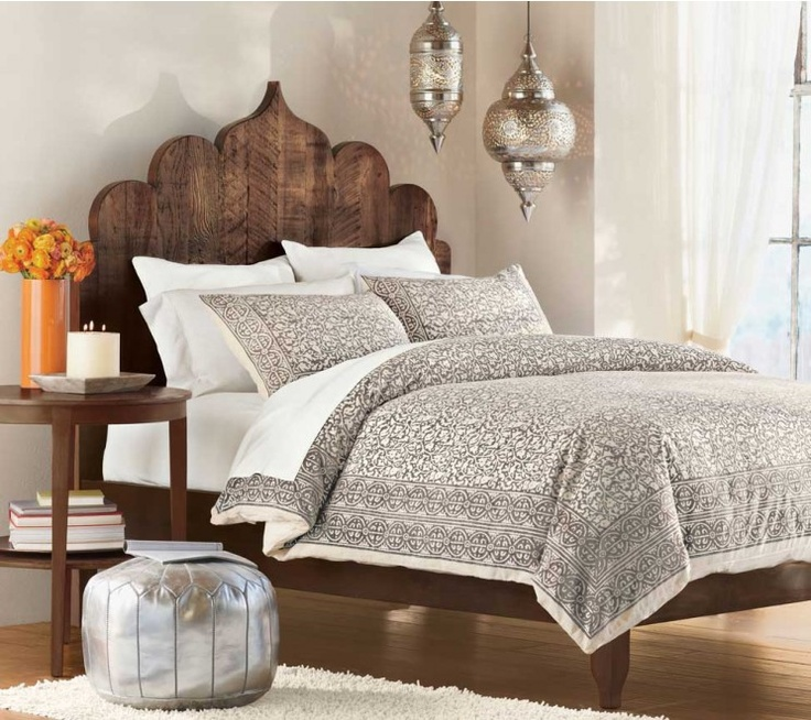 a reclaimed wodo carved bed, silver lanterns and ottomans make a rustic bedroom more Moroccan like