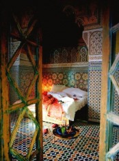 a colorful bedroom fully clad with bright mosaic tiles, a low table and lots of candles feels totally Moroccan-like