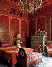 a red and marigold bedroom with carved wooden furniture and a crystal chandelier screams Moroccan
