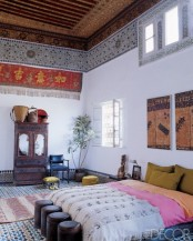 the floor clad with Moroccan tiles, colorful panels on the ceiling and walls, carved furniture and bright textiles