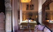 a chic Moroccan bedroom with lavender accents, mosaic tiles and pillars plus carved wooden shutters