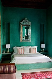 an emerald green Morocccan bedroom with plaster walls, printed textiles, an ornate mirror and elegant lamps