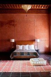 a rust-colored and red Moroccan living room with a leather bed, a boho rug and a lantern