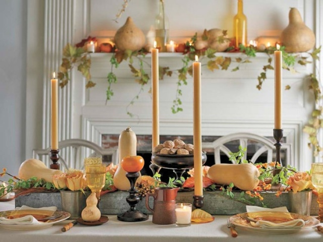 a warm colored tablescape with bright squashes, bold candles, leaves and some matching blooms is chic and cozy