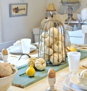 white pumpkins in a cage and gourds are great to style your Thanksgiving table and make it chic and cool