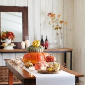 bold heirloom pumpkins and berries placed on a white table runner are amazing for a natural and chic Thanksgiving table