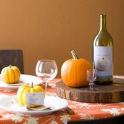 a wood slice as a stand, orange pumpkins and gourds are what you need to make your tablescape feel very cozy and natural