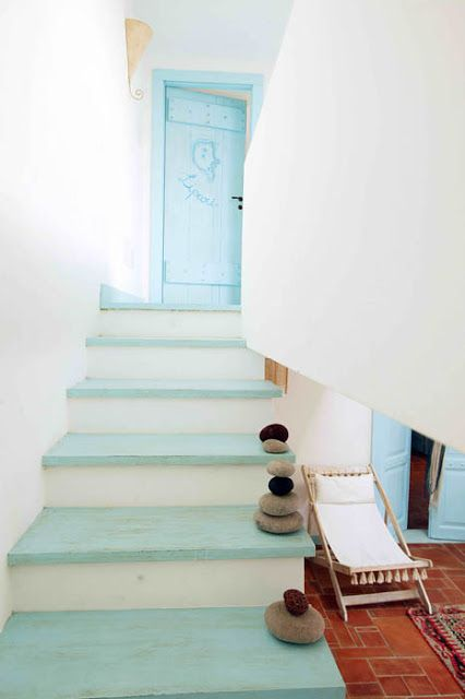 a nautical staircase with light blue steps and pebbles right on them and a light blue door