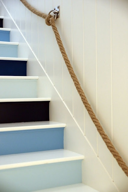 a nautical staircase with black, navy, blue and light blue steps and rope attached to the wall as railing