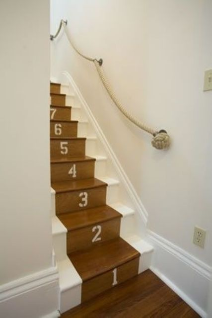 a nautical staircase, stained and white, with a thick rope rail attached to the wall is a cool idea