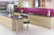 a bold kitchen done in tan, with stainless steel appliances and surfaces plus a fuchsia backsplash that wows