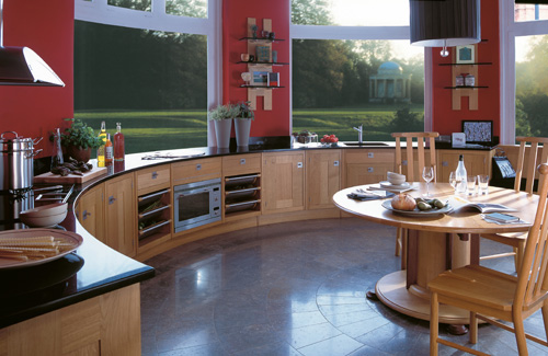 a curved kitchen with wooden cabinets, black coutnertops and red walls plus a gorgeous view is a fabulous place
