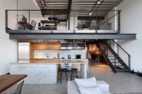 open urban kitchen design with concrete floors and faux brick surfaces