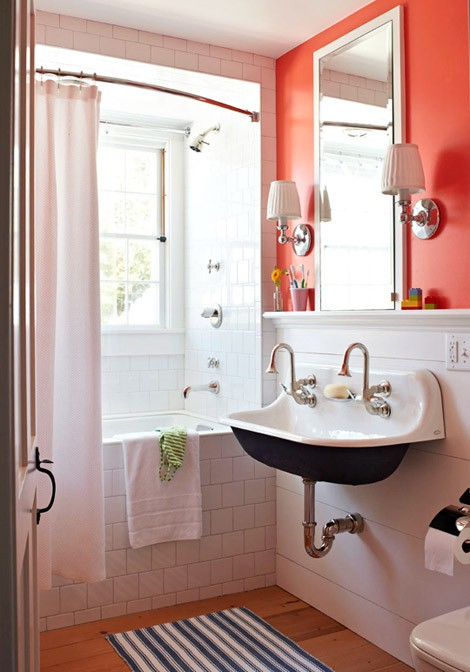 a bright orange wall in the sink zone accents it and make the neutral vintage bathroom brighter and whimsier