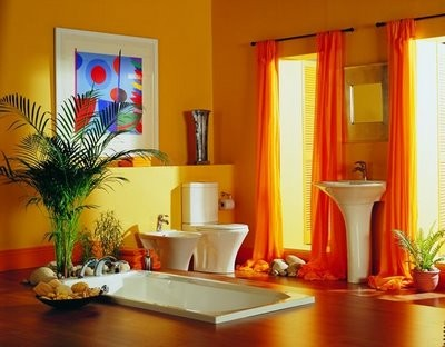 a warm-colored bathroom with orange curtains and an orange stripe that connects dark stained floors and warm-colored walls