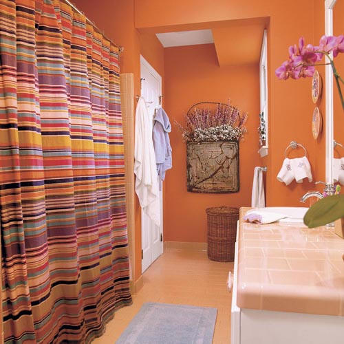a rust-colored bathroom with a warm-colored floor and a bright striped curtain that includes orange touches
